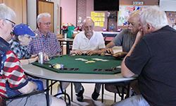 Table of active adults playing Texas Hold Em Poker